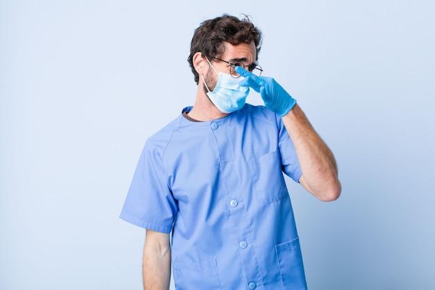 Giovane che si sente disgustato, trattenendo il naso per evitare di annusare un cattivo odore sgradevole. concetto di coronavirus