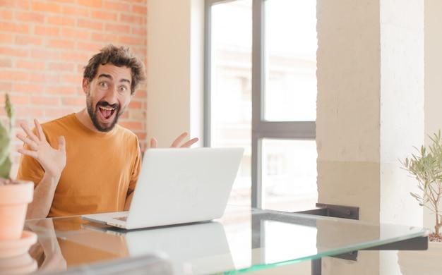 Giovane che si sente felice eccitato sorpreso o scioccato sorridente e stupito per qualcosa di incredibile