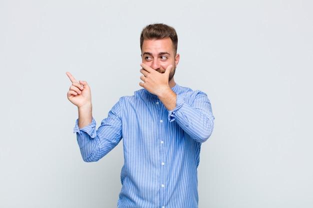 Giovane che si sente felice, scioccato e sorpreso, coprendo la bocca con la mano e indicando lo spazio laterale della copia