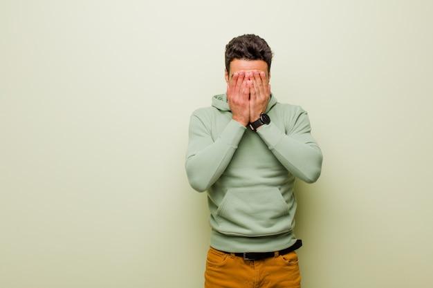 Giovane uomo triste, frustrato, nervoso e depresso, che copre il viso con entrambe le mani, piangendo contro la parete piatta