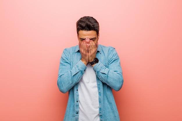 Giovane uomo triste, frustrato, nervoso e depresso, che copre il viso con entrambe le mani, piangendo sul muro rosa