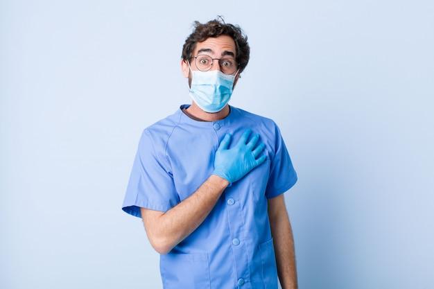 Giovane sentirsi scioccato e sorpreso, sorridendo, prendendosi per mano, felice di essere quello o mostrando gratitudine. concetto di coronavirus