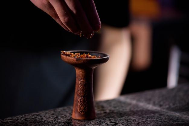 Giovane che riempie la ciotola di ceramica bruciata nera per il narghilè