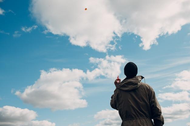 Giovane che pilota un aquilone contro il cielo blu.