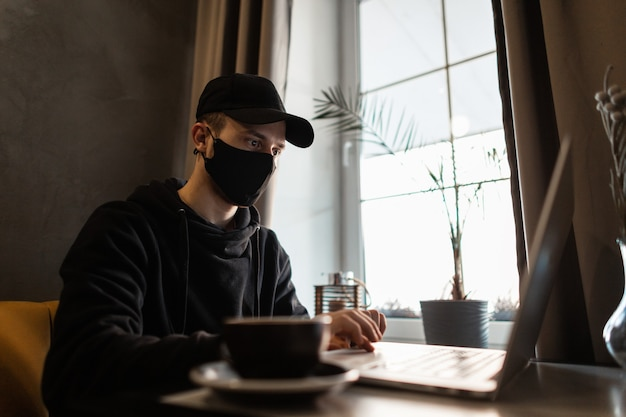 Giovane professionista freelance con maschera medica nera e berretto in felpa con cappuccio alla moda che lavora al computer portatile e beve caffè al bar. pandemia e concetto di protezione