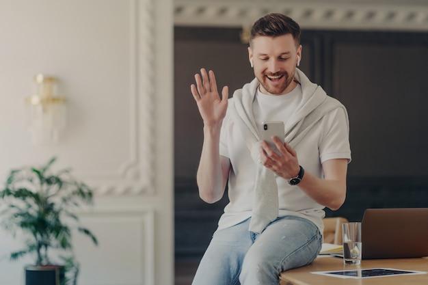 Giovane libero professionista che guarda lo smartphone e saluta i colleghi durante la conferenza web, il lavoratore a domicilio seduto sulla scrivania indossando una maglietta bianca e con un maglione sulle spalle