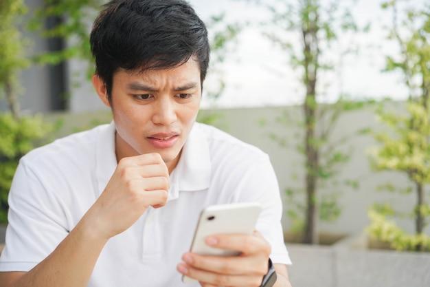 Giovane uomo aggrottò la fronte leggendo il commento sui social media per il concetto di cyber bullismo
