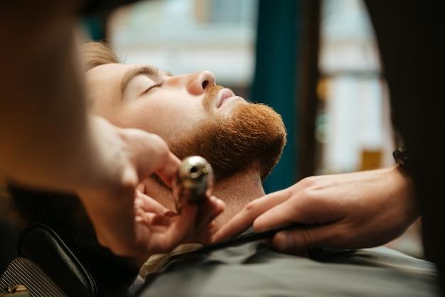 Giovane che si fa tagliare la barba dal parrucchiere mentre si trova sulla sedia al barbiere.