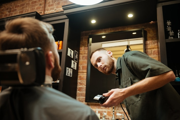 Giovane che si fa tagliare la barba dal parrucchiere mentre è seduto in poltrona al barbiere.