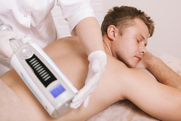 Giovane che ottiene massaggio endosfere presso la clinica di bellezza