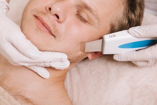 Giovane uomo che ottiene trattamento per la cura della pelle del viso dal cosmetologo