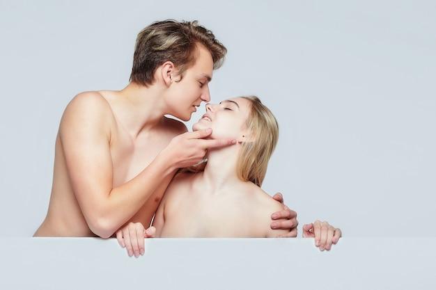 Il giovane e la ragazza stanno dietro i cartelloni pubblicitari bianchi. mostrando segni di attenzione reciproca. il concetto di pubblicità, psicologia delle relazioni. sfondo bianco