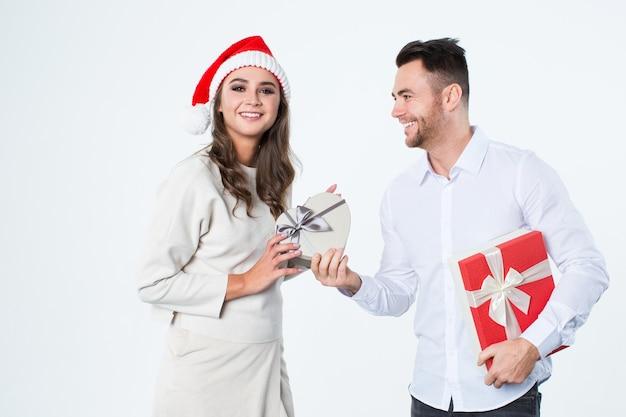 Il giovane dà i regali a una ragazza su una priorità bassa bianca. felice anno nuovo e buon natale.