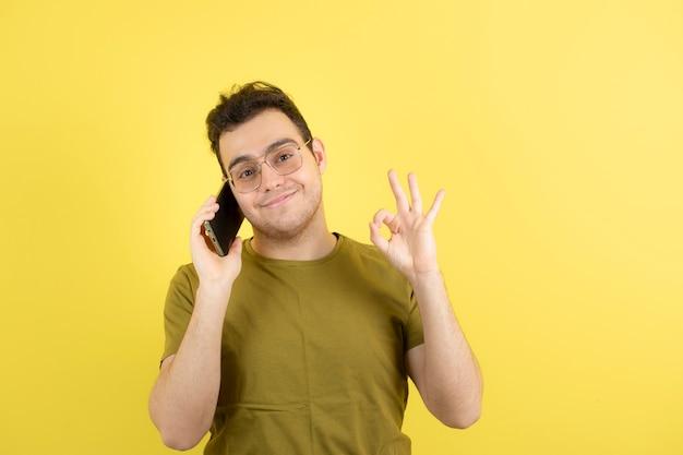 Giovane uomo con gli occhiali a parlare con qualcuno sul cellulare.