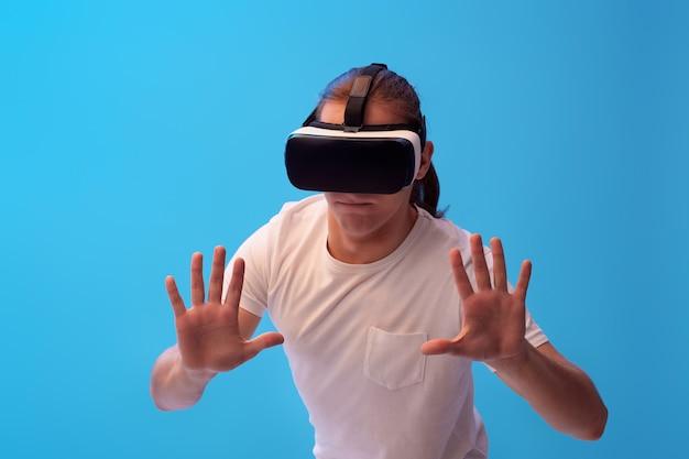 Giovane in bicchieri di realtà virtuale per giocare ai videogiochi su sfondo blu.