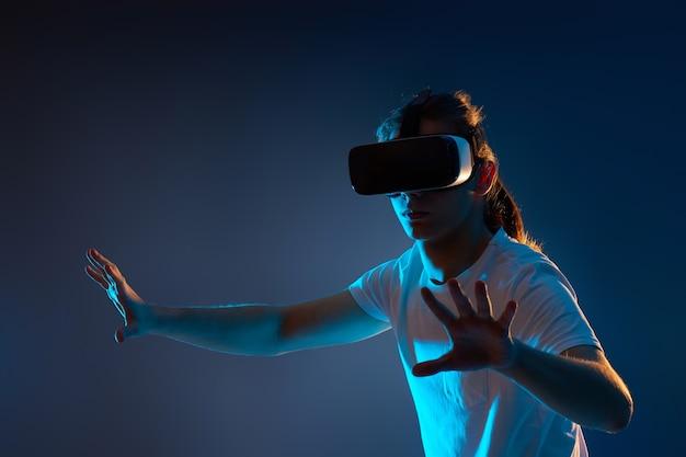 Giovane uomo in bicchieri di realtà virtuale che gioca ai videogiochi su sfondo blu scuro. luce al neon.