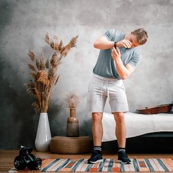 Un giovane fa sport a casa, si allena online dal telefono. l'atleta indossa un orologio sportivo, si prepara per l'allenamento in camera da letto, sullo sfondo c'è un letto, un vaso, un tappeto.