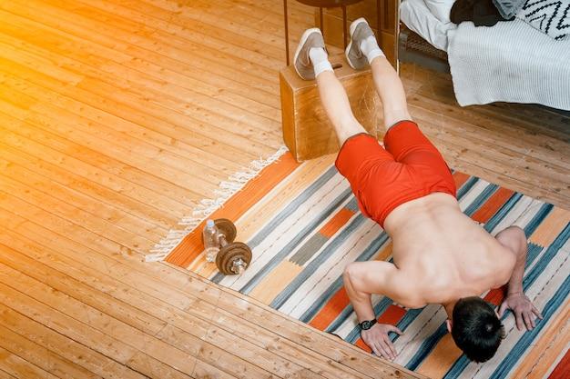 Il giovane va a fare sport a casa. uno sportivo con i capelli blac fa flessioni sul tappeto in camera da letto, vista dall'alto