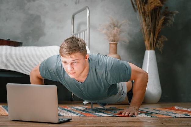 Il giovane va a fare sport a casa. uno sportivo con i capelli biondi fa flessioni e guarda film, guardando un allenamento online sul tappeto in camera da letto