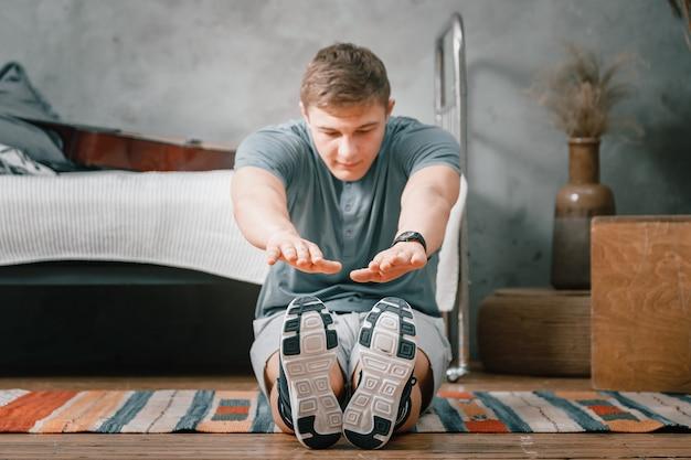 Il giovane va a fare sport a casa. sportivo con i capelli biondi si allunga con le dita in calzini sul tappeto in camera da letto