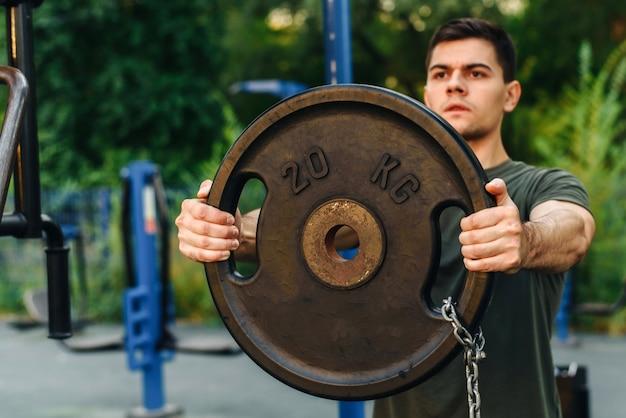 Un giovane fa sport, pompa i muscoli con l'aiuto di un pesante disco con bilanciere. all'aperto