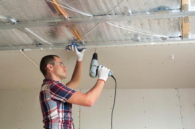 Giovane uomo in occhiali di protezione che fissa il controsoffitto del muro a secco al telaio metallico utilizzando un cacciavite elettrico sul soffitto isolato con un foglio di alluminio lucido. ristrutturazione, costruzione, concetto fai da te.