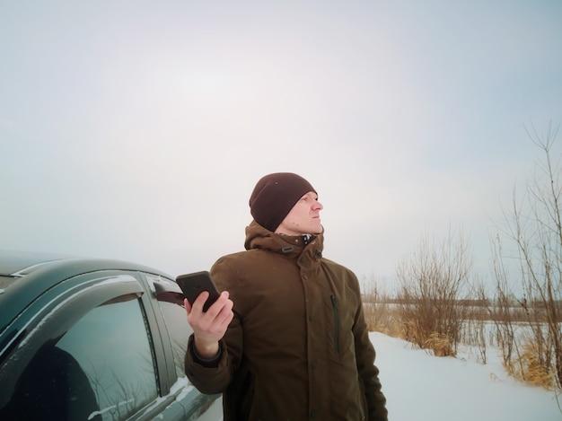 Un giovane si è perso in macchina in inverno e sta cercando di raggiungere la rete mobile dopo essere sceso dall'auto. concetto di viaggio su strada invernale, ricerca stradale, navigazione.