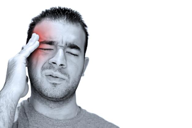 Un giovane si afferra la testa angosciato dal dolore o addirittura dallo stress. isolato su bianco con copyspace.
