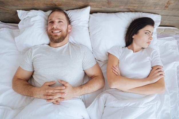 Giovane che sorride ampiamente e guarda il soffitto mentre sua moglie lo guarda arrabbiata