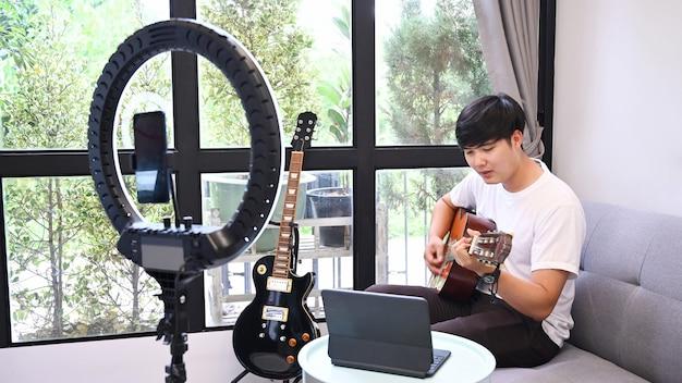 Chitarrista giovane che suona la chitarra e registra video per il suo blog.