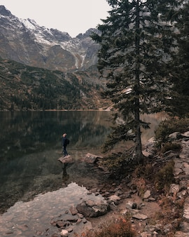 Un giovane uomo con un cappuccio si trova sulla grande pietra nel mezzo di un limpido lago verde azzurro circondato da alte montagne