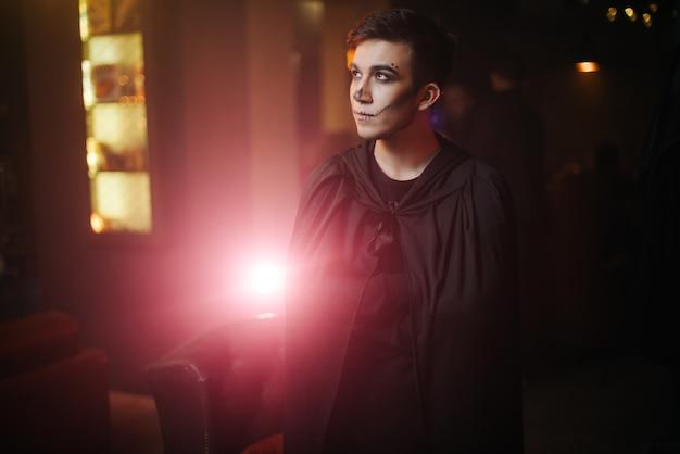 Il giovane in un vestito nero di halloween distoglie lo sguardo dalla telecamera. sul viso del ragazzo c'è un trucco colorato.