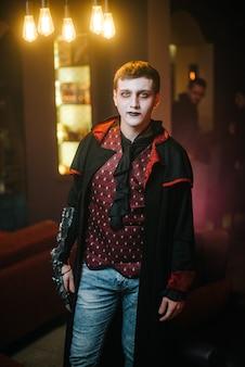 Il giovane in un costume di halloween del conte dracula con una faccia seria guarda la telecamera