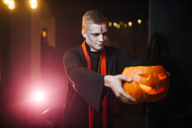 Giovane in un costume di halloween che tiene una zucca intagliata sul braccio teso. la zucca è sfocata, l'obiettivo della telecamera è sul viso del ragazzo.