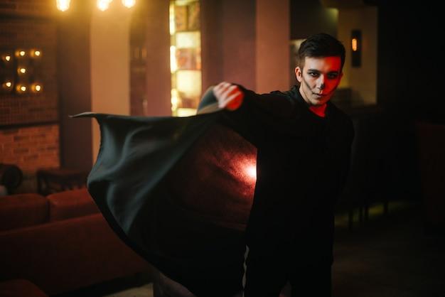 Il giovane in un costume di halloween sta sviluppando il suo mantello e sta guardando la telecamera. sul viso del ragazzo c'è un trucco colorato.