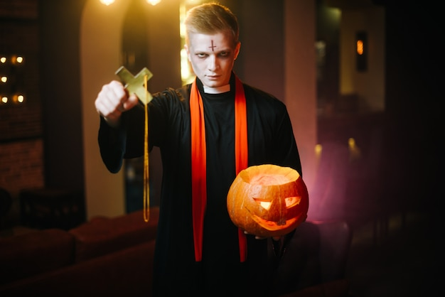 Giovane uomo in costume da sacerdote di halloween che tiene zucca intagliata davanti alla telecamera. il ragazzo guarda nella telecamera