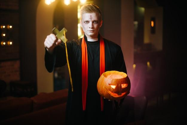 Il giovane in un costume da prete di halloween tiene una zucca intagliata festiva e una grande croce nera religiosa. il ragazzo sotto forma di prete guarda la telecamera