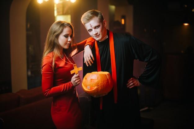 Il giovane in costume da prete di halloween tiene in mano una zucca intagliata e guarda la telecamera. una ragazza con un vestito rosso si appoggia sulla spalla del ragazzo