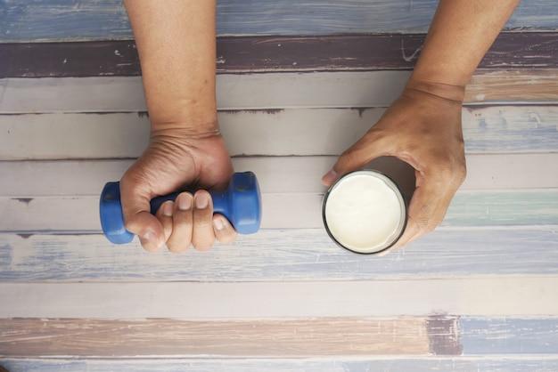 Mano del giovane che si esercita con i dumbbells e che tiene il bicchiere di latte