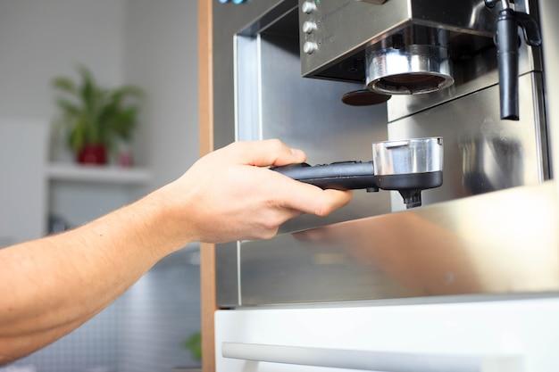 Mano del giovane che prepara un coffeeat la sua cucina moderna