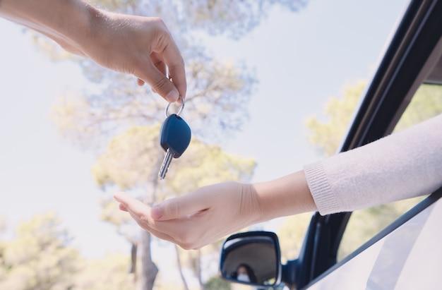 Giovane che consegna le chiavi di un'auto che indossa una maschera protettiva
