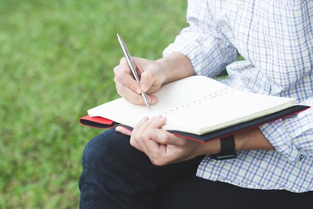 Le mani del giovane tengono le pagine aperte del taccuino con la matita blu nella tavola di legno chiara con i segnalibri