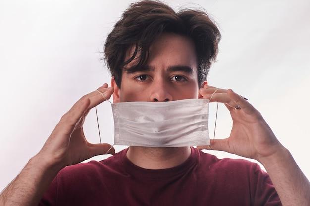 Il giovane passa mettere la nuova maschera del respiratore per la copertura del naso e della bocca nel tempo di quarantena del virus. prima protezione. concetto di assistenza sanitaria. avvicinamento. vista frontale.