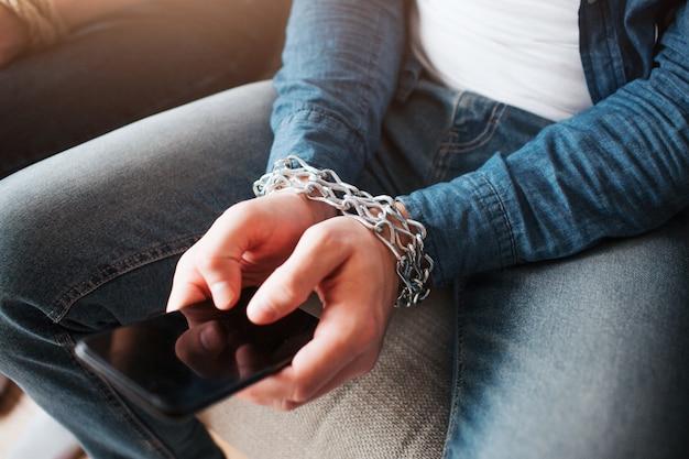 Il giovane ha una dipendenza dai social media. telefono in mano. catene intorno al polso. ostaggio dei social media. seduto sul divano. taglia vista.