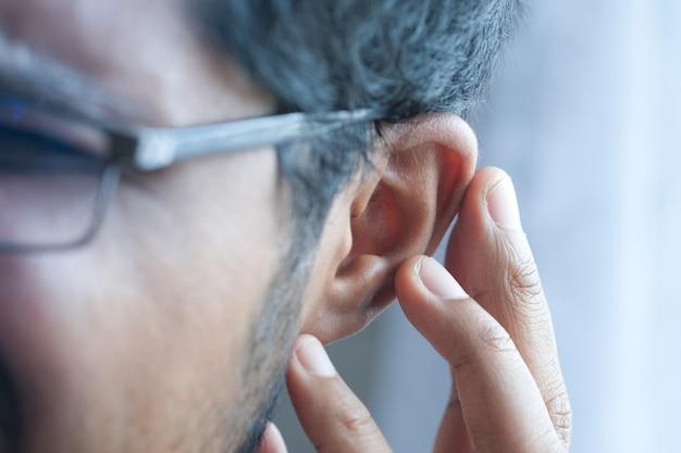 Giovane che ha dolore all'orecchio toccando il suo orecchio doloroso
