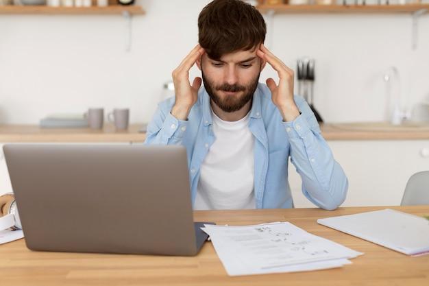 Giovane che ha mal di testa mentre lavora