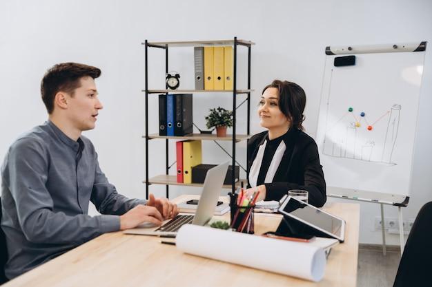 Giovane che ha un'intervista o una riunione d'affari con il datore di lavoro. datore di lavoro che esamina in un interno moderno dell'ufficio