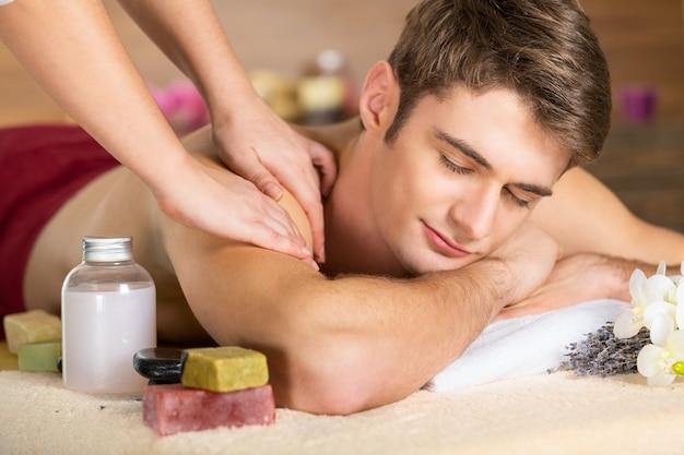 Giovane che ha un massaggio nel salone della stazione termale