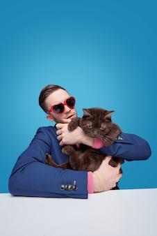 Giovane uomo in occhiali da sole a forma di cuore seduto al tavolo e che tiene gatto dispiaciuto