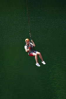Un giovane con un casco è saltato dal bungee jumping e ora è appeso a una corda, oscillando e riprendendosi su una videocamera sportiva su uno sfondo sfocato d'acqua